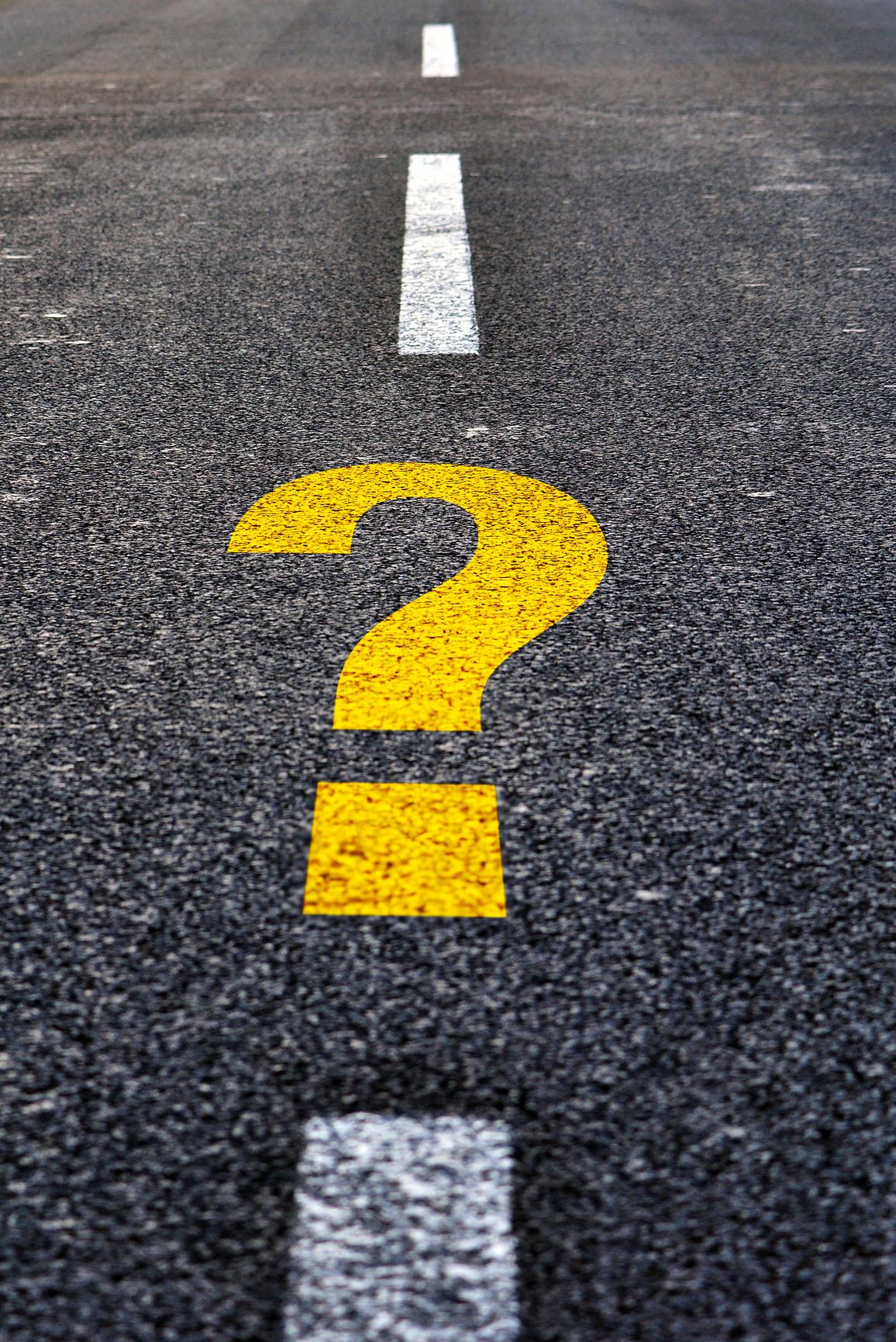 Question mark drawn on a black asphalt road